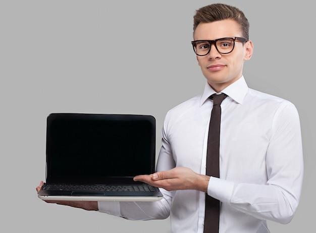 Człowiek z laptopem. przystojny młody mężczyzna w koszuli i krawacie, trzymający laptopa i wskazujący go, stojąc na szarym tle