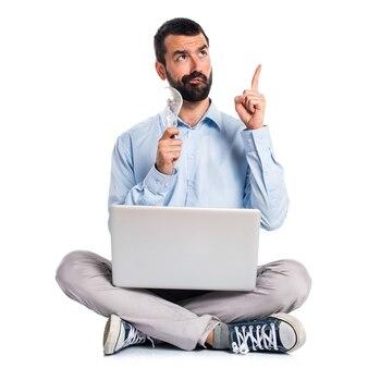 Człowiek z laptopem trzyma żarówkę