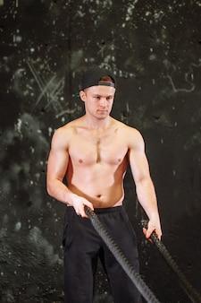 Człowiek z lin bitewnych ćwiczenia w siłowni fitness