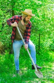 Człowiek z łopatą w ogrodzie.