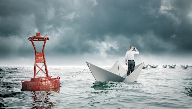 Człowiek z lornetkami na papierowej łodzi przywiązanej do boi. łodzie, które odpływają. pojęcie aspiracji i przeciwności.