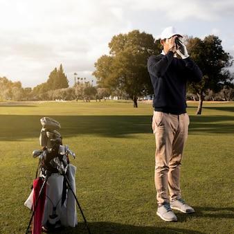 Człowiek z lornetkami na polu golfowym