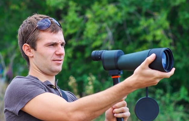 Człowiek z lunetą patrzy na cel. pozytywny człowiek z teleskopem