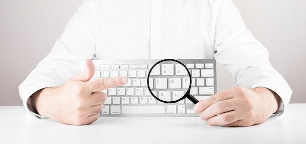 Człowiek z lupą i białą klawiaturą komputera