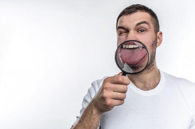 Człowiek z lupą patrzy przed siebie i pokazuje język przez szybę