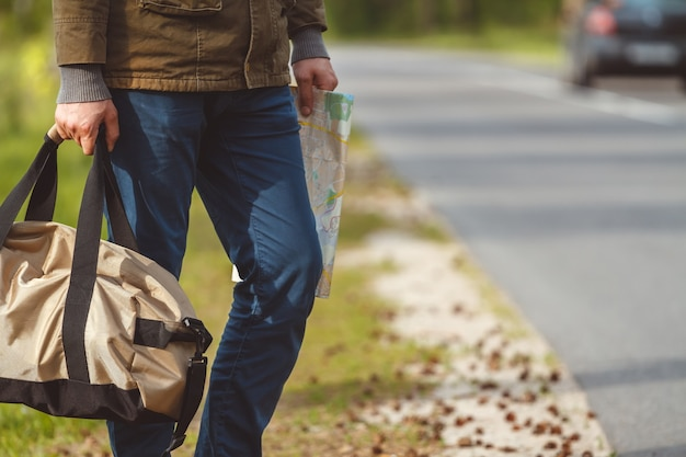 Człowiek z mapą i torbą w ręku, chodzenie na poboczu drogi
