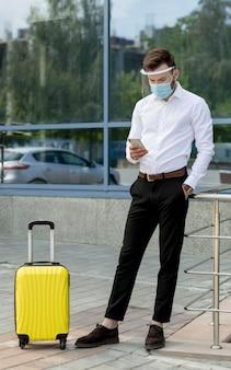 Człowiek z maską i bagażem za pomocą telefonu komórkowego