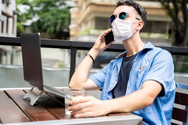 Człowiek z maską i okularami przeciwsłonecznymi, pracujący zdalnie ze swoim laptopem i rozmawiający z telefonem komórkowym na zewnątrz