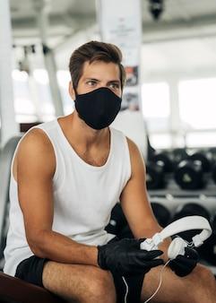 Człowiek z maską medyczną i słuchawkami na siłowni