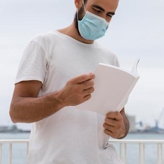Człowiek z maską medyczną nad książką do czytania jeziora