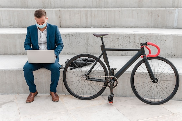 Człowiek z maską medyczną pracuje na laptopie obok roweru