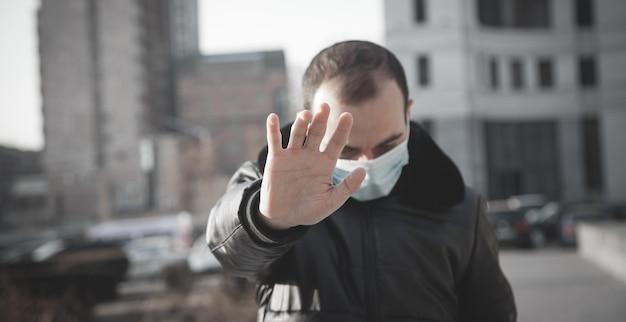 Człowiek z maską medyczną robi gest stopu.