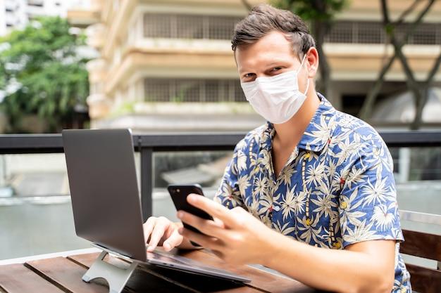 Człowiek z maską ochronną na twarzy, pracujący zdalnie z laptopem i korzystający z telefonu komórkowego