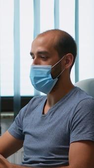 Człowiek z maską ochronną podczas spotkania wideo siedzi samotnie w biurze. freelancer pracujący w nowym, normalnym miejscu pracy, rozmawiający na czacie, prowadzący wirtualną konferencję, webinar, wykorzystujący technologię internetową