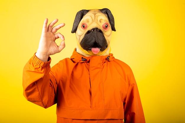 Człowiek z maską psa na białym tle na żółtej ścianie. gest człowieka z ok znak, dobry wybór.