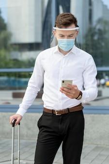 Człowiek z maską sprawdzanie telefonu komórkowego