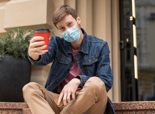 Człowiek z maską wiwatującą przy filiżance kawy