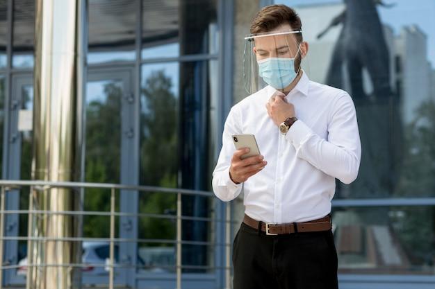 Człowiek z maską za pomocą telefonu komórkowego