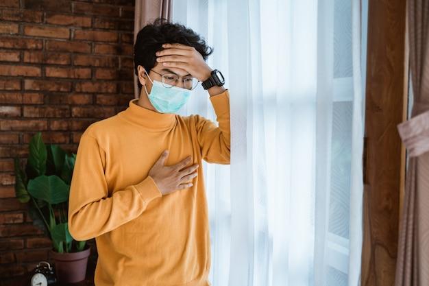 Człowiek z maskami twarzy patrząc przez okno