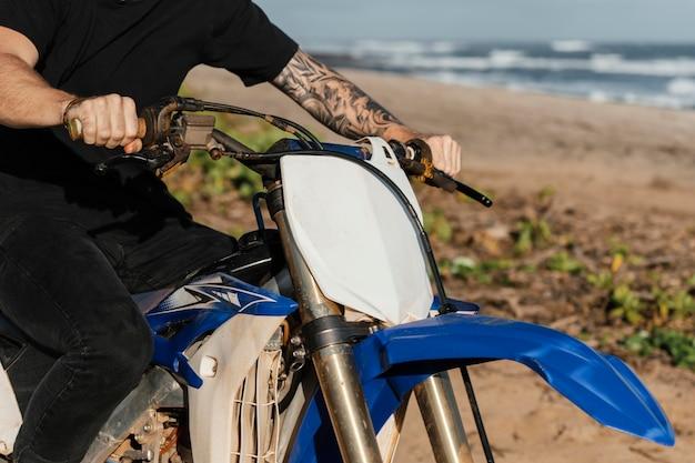 Człowiek z motocyklem na hawajach z bliska