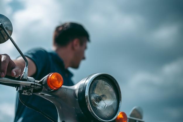 Człowiek z motocyklem, patrząc z boku