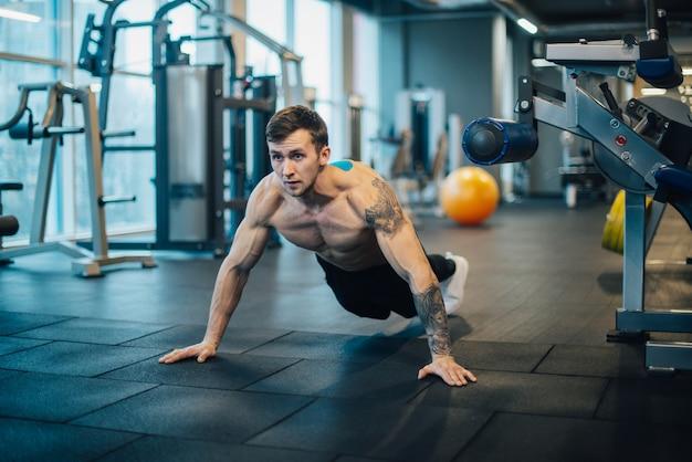 Człowiek z nagi tors wykręcony z podłogi w siłowni