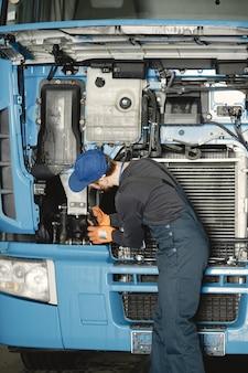 Człowiek z narzędziami do ciężarówki. pracownik w mundurze. wadliwa ciężarówka