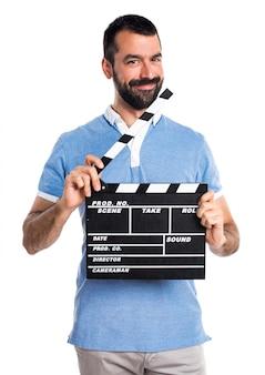 Człowiek z niebieską koszulę trzyma klapperboard