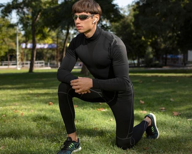 Człowiek z okularami przeciwsłonecznymi, ćwicząc na świeżym powietrzu, mając na sobie słuchawki