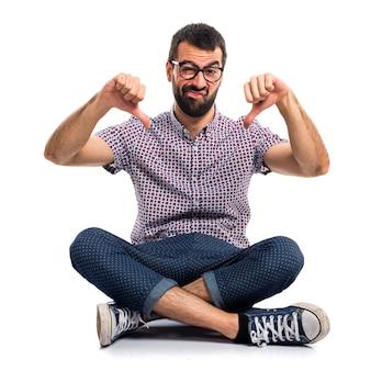 Człowiek z okularami robi złego sygnału