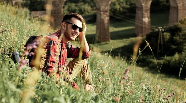 Człowiek z okulary siedzi w zielonym polu