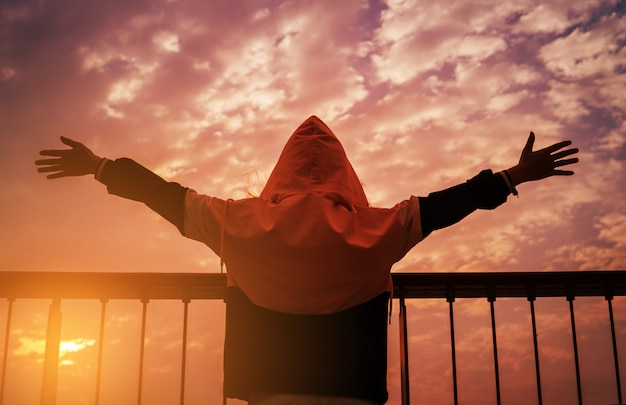 Człowiek z otwartymi ramionami o zachodzie słońca