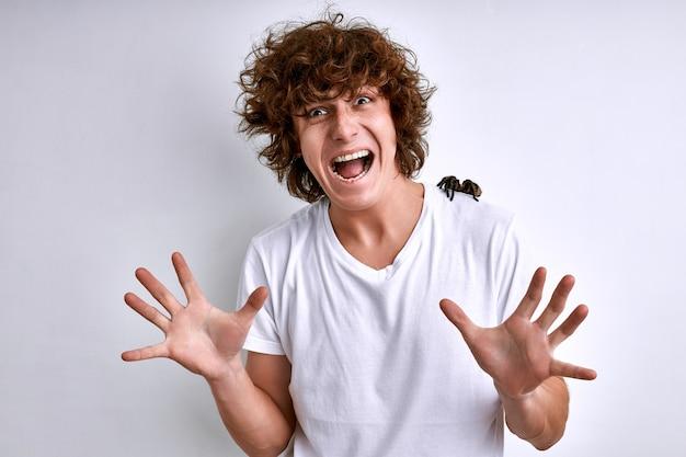 Człowiek z pająkiem na ramionach na białym tle. przestraszony młody człowiek ma fobię