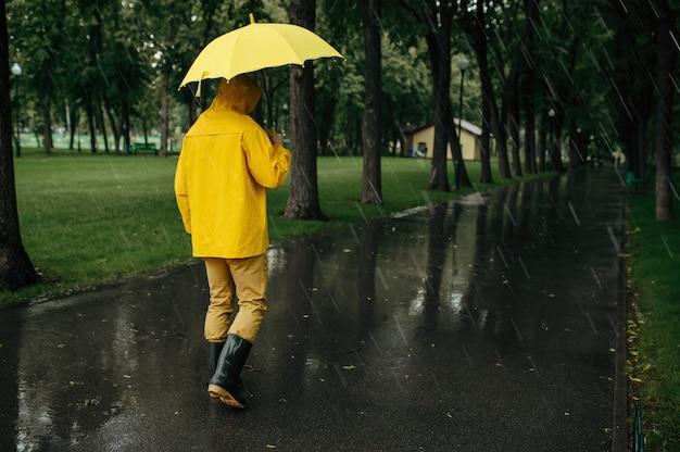 Człowiek z parasolem spaceru w parku lato w deszczowy dzień. mężczyzna w pelerynie przeciwdeszczowej i kaloszach, deszczowa pogoda w alei