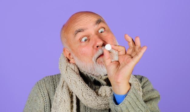 Człowiek z pigułkami. zimowy chłód. grypa. pigułka lecznicza. lekarstwo.