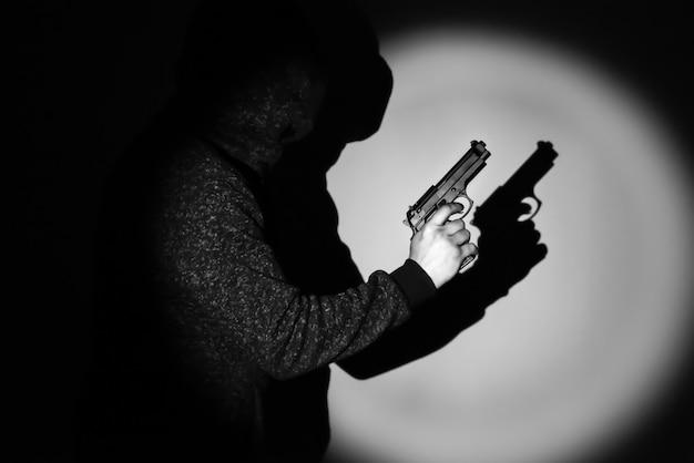 Człowiek z pistoletem. cień w świetle reflektorów. pojęcie karne.