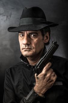 Człowiek z pistoletem i poważny wygląd