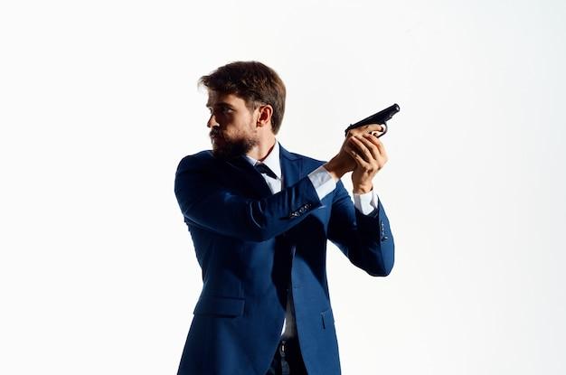 Człowiek z pistoletem w ręku detektyw kryminalny zabójca jasne tło