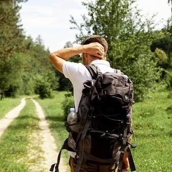 Człowiek z plecakiem na leśnej drodze