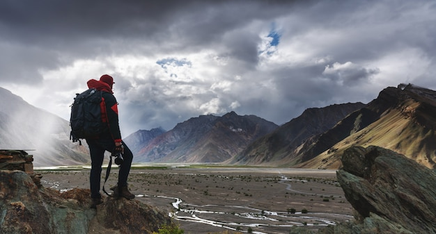 Człowiek z plecakiem trzymając aparat stojący na klifie z widokiem na góry i światło słoneczne przez chmurę.