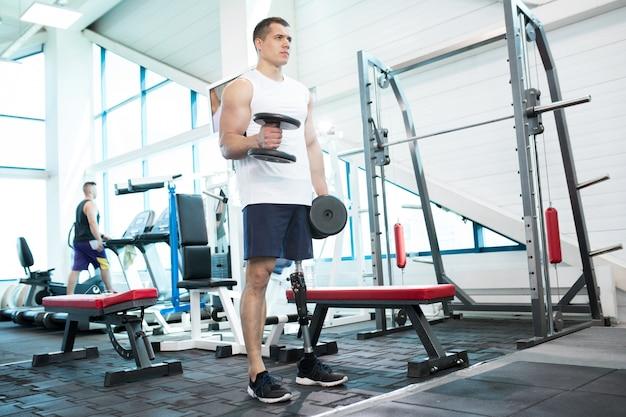 Człowiek z protezą nóg w siłowni