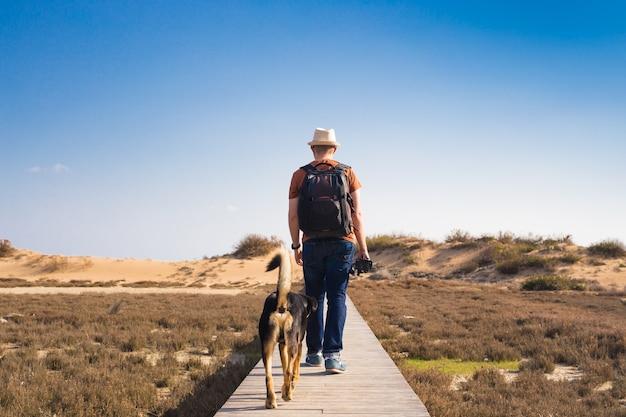 Człowiek z psem na drewnianej ścieżce na plaży i patrząc na odległość oceanu.