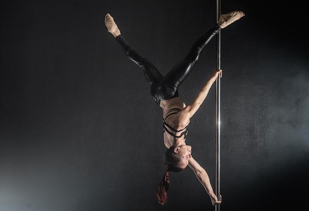 Człowiek z pylonem. męski słupa tancerza taniec na czarnym tle