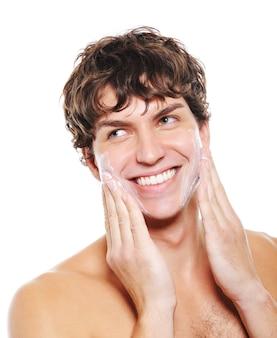Człowiek z radosnym uśmiechem stosując balsam nawilżający po goleniu na twarz