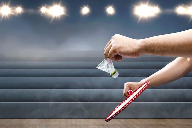 Człowiek z rakiety do badmintona, trzymając wolant i gotowy w pozycji służącej