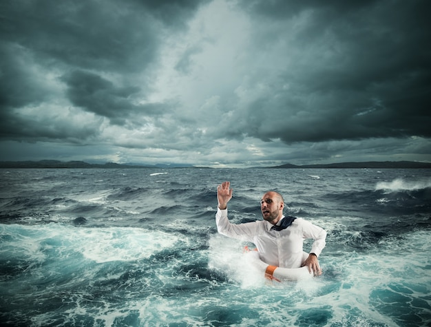 Człowiek z ratownikiem o pomoc na wzburzonym morzu