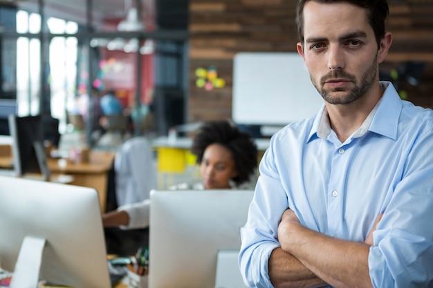 Człowiek z rękami skrzyżowanymi stojąc w biurze