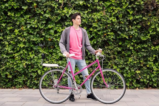 Człowiek z rocznika roweru na tle zielonych roślin