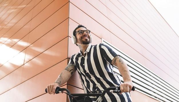 Człowiek z rowerem i słuchawkami szczęśliwy na ulicy