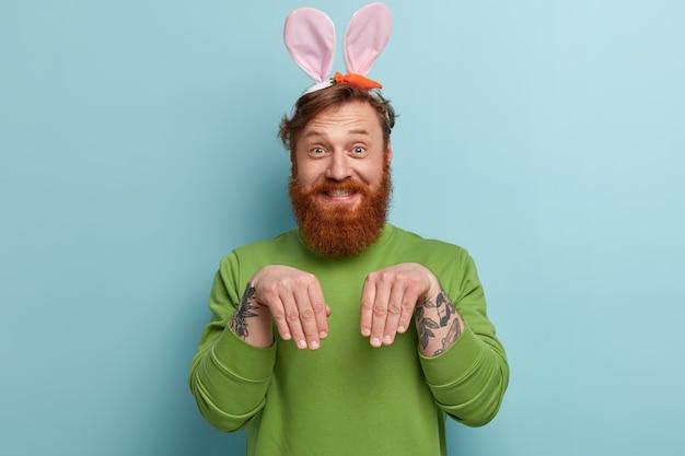 Człowiek z rudą brodą na sobie kolorowe ubrania i uszy królika